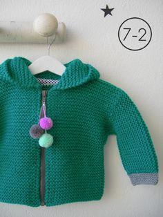 Cazadora para bebe hecho a punto bobo de color verde con capucha. Puños y pompón de capucha en gris plata y, pompones de distintos colores en cremallera. Interior en lunares.
