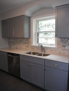 A worn out 1950's ranch kitchen was reinvented into a chic yet charming space. Quartz counter tops, new gray cabinets, with high end chrome handles slate flooring and gray patterned wall tiles  I love the gray, not your typical kitchen at all!