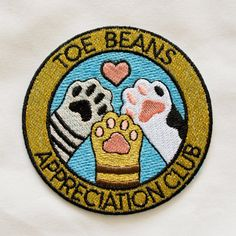 Toe Beans Appreciation Club iron-on patch! 3 in height. Iron-on patch instructions: Step 1: Set your hand iron at the hottest temperature setting. DO NOT USE STEAM DURING APPLICATION! Step 2: Place patch in the desired position and place a pressing cloth (such as a handkerchief, sheet or pillowcase fabric) over top. Step 3: Press the iron straight down for 35-45 seconds with as much constant pressure as possible. NO BACK AND FORTH. Step 4: Turn the garment inside-out and repeat steps 2 &...