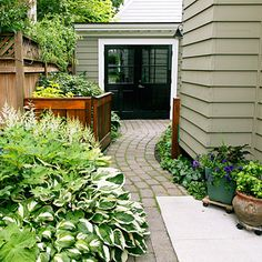 curving path, pretty gate. Colors of trim+door+house.  Love the lush, strong for winter plants.  plants on wheels too.  Tall Fence is a Must!