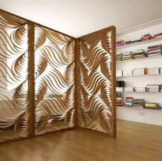 These room divider ideas include the use of bookcases, strips of cloth, unique fabrications, brilliant colors and strategic placement within the home.