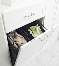 From 'BHG', this tilt out storage bin was built into an existing wall, between the two studs. This is something a DIY'er can do, but make sure you cross your t's and dot your i's… You don't want to open up a wall that has electrical or plumbing lines run through it!