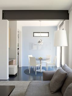 rho architects, exposed steel beam, dining area, grey sofa, white walls, blue accent wall, dark floors