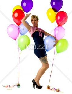 woman with mouth open standing with balloons. - Portrait of a woman with mouth open standing besides balloons over white background, Model: Carrie Galbraith