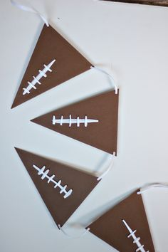 Football season is right on our horizon, I can even small the grills and pom poms! While I'm not the biggest football fan, I do love to throw a little party! If you find yourself tailgating at home, craft up this simple football pennant garland. This tutorial looks just like the lacing on a ...