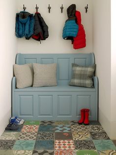 Colorful mud room with blue storage bench below oil-rubbed bronze coat hooks over a patchwork tiled floor.
