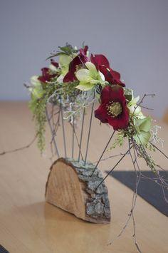 Dekorace na stůl (či jinam) Dekorace na stůl či poličku, pohledově oboustranná, látkové květy a zeleň na konstrukci z drátů, na dřevěném podstavci. Šířka celé dekorace je 45 cm - výška 30 cm.