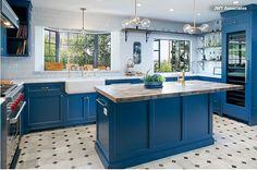 """The vibrant cabinet paint color the homeowners chose is """"Stiffkey Blue"""" by Farrow & Ball. They replaced the peninsula with an island that opens the kitchen to the adjoining breakfast room and turned it into one big, open space."""