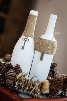 White painted wine bottles with twine wrap and a charm.