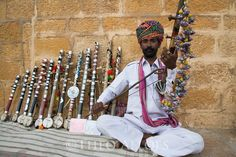 Rajasthani musician playing and selling chikara string instrument on street