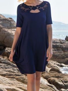 Modèle de robe en modal et élasthanne uni marine de la célèbre maison italienne Oscalito. Le décolleté du modèle est rond travaillé en macramé de fleurs ton sur ton plus trou de forme ovale juste au