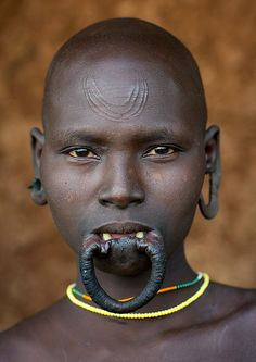 Suri Tribe Woman with enlarged lip and earlobe openings, and scarification on forehead. Kibish, Omo Valley, Ethiopia by Eric Lafforgue We Are The World, People Around The World, Art Tribal, Tribal Face, Culture Art, Eric Lafforgue, Tribal People, African Tribes, African Culture