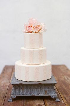 Delicate pink and white striped wedding cake. Stripes are neat. A different cake dish would be nice