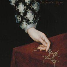 """Dettagli 3. Marcus Gheeraerthes il giovane: Ritratto di Mary Rogers, lady Harington. Olio su tavola del 1592. Tate Britain, Londra. La manica è estremamente complessa, con il velo che esce da strisce di tessuto nero intagliate ed in sbiego: finisce in un sottile polsino dal pizzo quasi invisibile. La mano regge un intreccio di nodi che si riferiscono al motto scritto più in alto, sul fondo scuro: """"Non Faceam Nec Frangam"""", che dovrebbe dire """"Non Fare Non Disfare"""", come intenzione futura."""