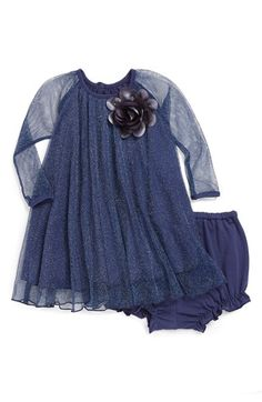 A shimmery mesh overlay and floral accent provide a festive update for a floaty dress paired with matching bloomers.