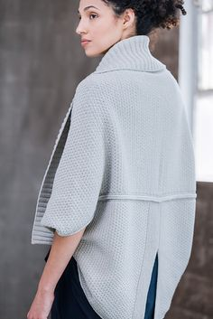 Wrap up two elegant ways in the same cocoon cardigan. With the ribbed edge upward, Shoji features a shawl collar, three-quarter length sleeves, and a garter hem deeply split into tails at the center back. Turn it upside down and the fronts hang with an intriguing zigzag, the sleeves bare your elbows, and the ribbing curves gracefully below hip length. The knitting is simplicity itself: a long rectangle of pebbled texture stitch folded and sewn into the final shape, with stitches picked up…