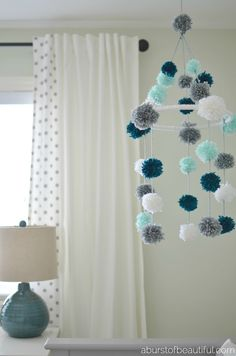 A DIY pom-pom mobile made from yarn and an embroidery hoop is a fun and stimulating addition to your little one's nursery. Find the full tutorial at Diy Décoration, Easy Diy, Diy Crafts, Diy Mobile, Mobile Craft, Orb Light Fixture, Pom Pom Mobile, Pom Pom Baby, Pom Pom Rug