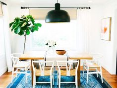Sunken living and dining room with antique accessories and greenery