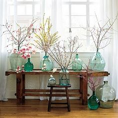 A wedding inspired this spring look. Simple colored glass bottles filled with twigs from some of my favorite bushes & trees.