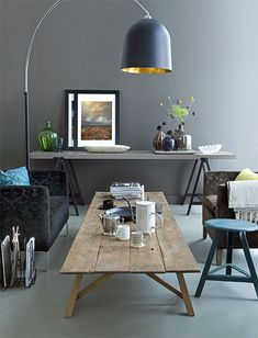 Gray walls provide the perfect backdrop for this living room - the huge dome light fixture gives a nod to decades past, while the exposed wood and worktable lend a more industrial feel.