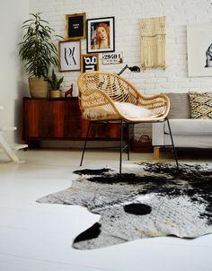 Woven chair, animal hide rug, mid-century sideboard, gallery wall