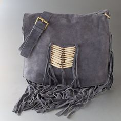 With bone-bead detailing and plentiful fringe, this classic over-the-shoulder bag in soft grey suede is an instant look maker. Coupled with its flash and fringe, the easy shape and roomy interior will guarantee this chic crossbody an anchor spot in many a standout look.