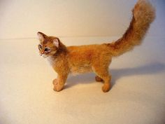 Dollhouse Miniature Somali Cat. Artisan handsculpted polymer 1:12th scale Somali cat. Cat's coat is cream alpaca wool with hand painted markings. Crystal clear green eyes are hand made and glossed. Tail is adjustable. Cat's whiskers are white tapered hairs. Cat has wire armature base and is made without the use of molds