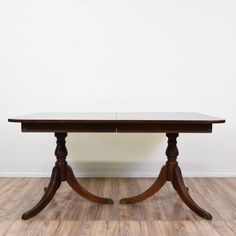 This Duncan Phyfe dining table is featured in a solid wood with a glossy mahogany finish. This wooden table has a carved trumpet turning base, triangular base w/ gold tipped feet, and a rounded rectangular table top. Perfect for the dining room! #traditional #tables #diningtable #sandiegovintage #vintagefurniture