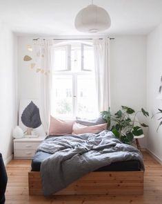 Light-drenched bedroom with warm wood floors and a matching bed frame.