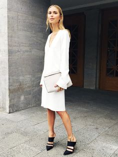 Pernille Teisbaek of Look de Pernille wears a white v-neck dress with black strappy mules and a neutral clutch