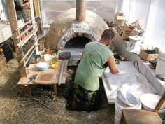 This design for a wood fired pizza oven not only works wonders for baking, but also provides heat to a greenhouse and attached home.