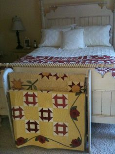 Quilt folded on a bed & more quilts displayed on a quilt rack at the foot of the bed