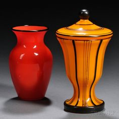 REAL Loetz Tango glass, Czechoslovakia, c. 1920-1940. The baluster-form red vase with black rim, polished pontil, ht. 5; the orange jar and lid with black enamel decoration, ht. 6 1/2 in., both with acid-stamped Czecho-slavakia mark in an oval on bases.