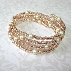 Beaded Bracelet with Four Rows of ivory beads and pearls on memory wire. $15.00, via Etsy.