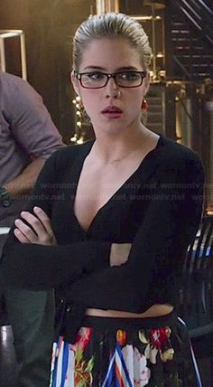 Felicity's black long sleeved wrap top and floral pleated skirt on Arrow.  Outfit Details: http://wornontv.net/45237/ #Arrow
