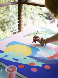 Leah painting on her back deck. Photo -Toby Scott, production – Lucy Feagins / The Design Files.