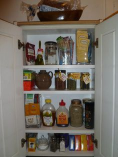 AFTER: Now the cabinet sits on top of the kitchen table, up against the wall and holds tea & supplies! Several of the jars are loose leaf teas, the two square vases are full of bags of tea, and all of the sweeteners and tea diffusers are in there. I love the little loose leaf tea jars... the two smaller ones are from Smuckers Simply Fruit jam, which is the only kind my roommate and I buy. As we go through our jam and other sauces in little jars, I will be reorganizing and adding more of my…