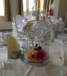 Vibrant Gerbera Bird Cage Table Wedding Reception Centrepiece | Wedding Flowers Liverpool, Merseyside, Bridal Florist, Booker Flowers and Gifts, Booker Weddings - Booker Weddings is Booker Flowers and Gifts website which is dedicated to our Wedding Flowers. We are based in Liverpool, Merseyside and would be happy to quote for Weddings in Liverpool and surrounding areas. We are Wedding Flower specialists and have been specially selected to be one of Interflora's Vera Wang Wedding Florists.