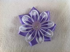 In this tutorial, you'll learn the technique of how to fold the petals and how to sew them together to make beautiful Kanzashi ribbon flowers. Then use the flowers to make hair clips, or to embellish handbags, or to decorate gifts.     Materials   	ribbon 	scissors 	thread 	needle 	craft glue
