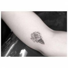 Tatuaje de una rosa de estilo fine line situado en el antebrazo, junto al codo. Artista tatuador: Dr. Woo