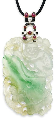 AN ART DECO JADE, GEM AND DIAMOND PENDANT, BY CARTIER, CIRCA 1925. The mid-19th century pierced Chinese jadeite jade panel carved to depict a boy climbing through scrolling foliage among lotus flowers and buds, suspended from a curved pendant loop set with onyx, cabochon ruby, single and old-cut diamond detail, to the black cord necklace, pendant 8.4cm, signed Cartier, Paris, London, New York. #Cartier #ArtDeco #pendant
