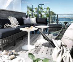 Terrazzo arredato con mobili per esterni in plastica intrecciata effetto rattan marrone-nero, con cuscini sedile/schienale neri