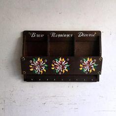 ヴィンテージのレターラック|カラフルなお花のトールペイントが入った素敵なレターラックです!Brev(手紙)、Regninger(メモ)、Diverse(その他諸々)と3つに仕切りの文字も可愛いですね。手紙やはがきを入れたり、メモを入れたり、はさみやペンなどの文房具、スマホを入れてもいいです!フックには鍵や、キッチンタオルなどを掛けることができます。レターラックとしても、キーハンガー、キッチン、玄関、お子様のお部屋でもお使いいただける万能ウォールシェルフですね。