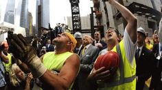 Iron worker Frank Gasior on left joins construction workers as the final steel beam is lifted by crane 977 feet in the air and placed atop 4 World Trade Center.