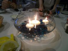 Centerpiece idea! Quick and easy! Credit goes to 2 of my sorority sisters who came up with these! Get a shallow curved glass, fill the bottom with blue glass gems, then fill to desired depth with water. Put floating candles in. Very pretty!