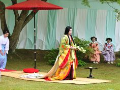 A woman playing the empress (or some other high ranking station) at a Kyokusui No En (a heian era poetry party.)