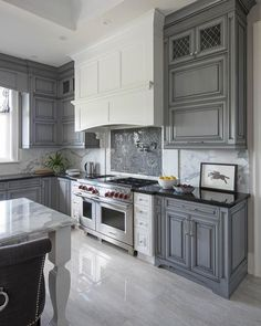 This #kitchen design embraces #modern taste combining the gray #cabinets with white accents black #countertops and a mosaic #backsplash that makes the #marble theme very visible.