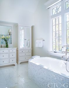 The light-filled master bathroom, painted in Benjamin Moore's Cloud White, features Waterworks fixtures and wall sconces.