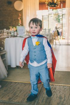 Page boy/ring bearer in blue bow tie and cape. Eclectic Colour Pop Barn Wedding | Whimsical Wonderland Weddings