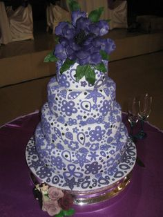 4 teir wedding cake with a Lilac Background and  Purple cut out flower decorations ~ all edible
